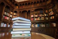 Συσσωρευμένα βιβλία με τη βιβλιοθήκη στο υπόβαθρο Στοκ εικόνα με δικαίωμα ελεύθερης χρήσης