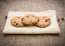 Συσσωρευμένα μπισκότα τσιπ σοκολάτας στην καφετιά πετσέτα πέρα από gunny backg Στοκ φωτογραφία με δικαίωμα ελεύθερης χρήσης
