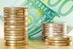 Συσσωρευμένα νομίσματα και ευρο- τραπεζογραμμάτιο Στοκ φωτογραφίες με δικαίωμα ελεύθερης χρήσης