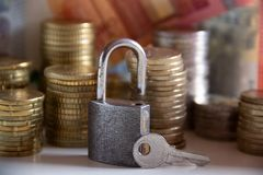 Συσσωρευμένα νομίσματα και τραπεζογραμμάτια πίσω από ένα λουκέτο με ένα κλειδί Στοκ εικόνες με δικαίωμα ελεύθερης χρήσης