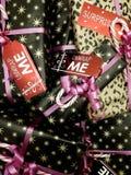 Συσσωρευμένα τυλιγμένα και διακοσμημένα δώρα Χριστουγέννων με τις χαριτωμένες ετικέττες στοκ εικόνες