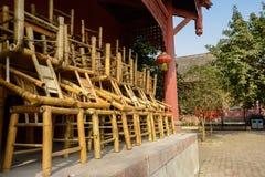 Συσσωρευμένες επάνω καρέκλες μπαμπού έξω από το ηλικίας κινεζικό κτήριο στην ηλιόλουστη DA Στοκ Φωτογραφία