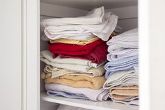 Συσσωρευμένες ζωηρόχρωμες πετσέτες μέσα σε ένα ντουλάπι στοκ φωτογραφίες