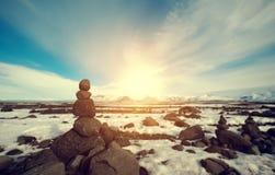 Συσσωρευμένη ο Stone ισορροπία στο χειμερινό τοπίο, με το φωτεινό φως του ήλιου στοκ εικόνα