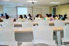 Συσσωρευμένοι άνθρωποι που παρευρίσκονται στο γεγονός σεμιναρίου Κενές καρέκλες στην τάξη με τους θολωμένους σπουδαστές μέσα Στοκ Φωτογραφίες