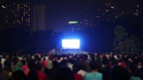 Συσσωρευμένοι άνθρωποι που προσέχουν τη TV έξω στην πόλη απόθεμα βίντεο