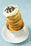 Συσσωρευμένος cupcakes σε ένα φλυτζάνι στοκ εικόνες