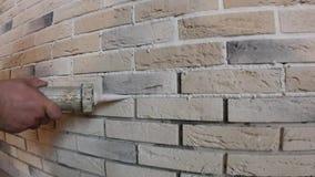 Συσσώρευση μιας διακοσμητικής πέτρας σε έναν τοίχο, εργασία επισκευής απόθεμα βίντεο