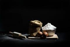 Συστατικά αρτοποιείων, αλεύρι, αυγά και ξύλινη κυλώντας καρφίτσα Στοκ Εικόνα