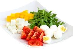 Συστατικά για μια σαλάτα σε ένα πιάτο σε ένα άσπρο υπόβαθρο Στοκ φωτογραφία με δικαίωμα ελεύθερης χρήσης