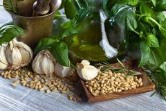 Συστατικά για την παραγωγή του pesto σε έναν ξύλινο πίνακα Στοκ Φωτογραφία