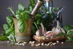 Συστατικά για την παραγωγή του pesto σε έναν ξύλινο πίνακα Στοκ Εικόνα