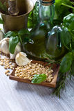 Συστατικά για την παραγωγή του pesto σε έναν ξύλινο πίνακα Στοκ Φωτογραφίες