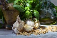 Συστατικά για την παραγωγή του pesto σε έναν ξύλινο πίνακα Στοκ Εικόνες