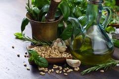 Συστατικά για την παραγωγή του pesto σε έναν παλαιό ξύλινο πίνακα Στοκ Εικόνες