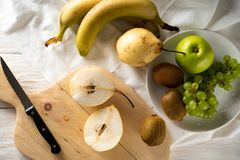Συστατικά για τη σαλάτα φρούτων Τέμνοντα αχλάδια σε έναν τέμνοντα πίνακα στοκ φωτογραφία με δικαίωμα ελεύθερης χρήσης