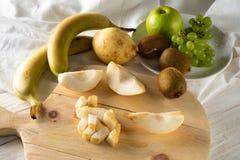 Συστατικά για τη σαλάτα φρούτων Τέμνοντα αχλάδια σε έναν τέμνοντα πίνακα στοκ φωτογραφίες με δικαίωμα ελεύθερης χρήσης