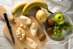 Συστατικά για τη σαλάτα φρούτων Τέμνοντα αχλάδια σε έναν τέμνοντα πίνακα στοκ εικόνες