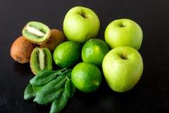 Συστατικά για το καταφερτζή Πράσινα φρούτα στο μαύρο ξύλινο υπόβαθρο Apple, ασβέστης, σπανάκι, ακτινίδιο detox τρόφιμα υγιή Στοκ Φωτογραφία