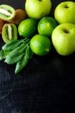 Συστατικά για το καταφερτζή Πράσινα φρούτα στο μαύρο ξύλινο υπόβαθρο Apple, ασβέστης, σπανάκι, ακτινίδιο detox τρόφιμα υγιή Τοπ ό Στοκ Εικόνα