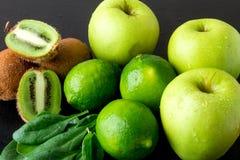 Συστατικά για το καταφερτζή Πράσινα φρούτα στο μαύρο ξύλινο υπόβαθρο Apple, ασβέστης, σπανάκι, ακτινίδιο detox τρόφιμα υγιή Στοκ φωτογραφία με δικαίωμα ελεύθερης χρήσης