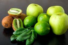 Συστατικά για το καταφερτζή Πράσινα φρούτα στο μαύρο ξύλινο υπόβαθρο Apple, ασβέστης, σπανάκι, ακτινίδιο detox τρόφιμα υγιή Στοκ Φωτογραφίες
