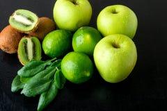 Συστατικά για το καταφερτζή Πράσινα φρούτα στο μαύρο ξύλινο υπόβαθρο Apple, ασβέστης, σπανάκι, ακτινίδιο detox τρόφιμα υγιή Στοκ Εικόνα