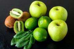 Συστατικά για το καταφερτζή Πράσινα φρούτα στο μαύρο ξύλινο υπόβαθρο Apple, ασβέστης, σπανάκι, ακτινίδιο detox τρόφιμα υγιή Στοκ Εικόνες