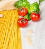 Συστατικά για το μαγείρεμα μακαρονιών με τα tomates, τα φύλλα βασιλικού και την παρμεζάνα Στοκ φωτογραφία με δικαίωμα ελεύθερης χρήσης