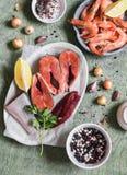 Συστατικά για το μαγείρεμα του μεσημεριανού γεύματος - φρέσκα κόκκινα ψάρια, γαρίδες, φασόλι, καρυκεύματα Σε έναν ξύλινο πίνακα,  Στοκ Φωτογραφία