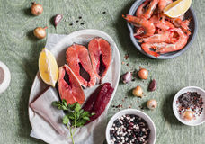 Συστατικά για το μαγείρεμα του μεσημεριανού γεύματος - φρέσκα κόκκινα ψάρια, γαρίδες, φασόλι, καρυκεύματα Σε έναν ξύλινο πίνακα,  Στοκ Εικόνα