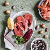 Συστατικά για το μαγείρεμα του μεσημεριανού γεύματος - φρέσκα κόκκινα ψάρια, γαρίδες, φασόλι, καρυκεύματα Σε έναν ξύλινο πίνακα Στοκ εικόνες με δικαίωμα ελεύθερης χρήσης