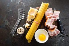 Συστατικά για το μαγείρεμα των ζυμαρικών Carbonara, των μακαρονιών με το pancetta, του αυγού και του σκληρού τυριού παρμεζάνας al Στοκ φωτογραφία με δικαίωμα ελεύθερης χρήσης