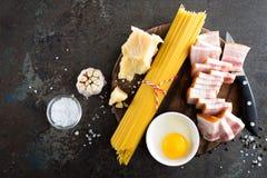 Συστατικά για το μαγείρεμα των ζυμαρικών Carbonara, των μακαρονιών με το pancetta, του αυγού και του σκληρού τυριού παρμεζάνας al Στοκ εικόνα με δικαίωμα ελεύθερης χρήσης