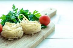 Συστατικά για το μαγείρεμα των ιταλικών ζυμαρικών - μακαρόνια, ντομάτες, βασιλικός και σκόρδο Στοκ Εικόνα