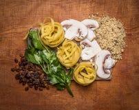 Συστατικά για το μαγείρεμα των χορτοφάγων ζυμαρικών με τα χορτάρια, μανιτάρια, ξύλα καρυδιάς, τοπ άποψη υποβάθρου σταφίδων ξύλινη Στοκ εικόνες με δικαίωμα ελεύθερης χρήσης