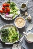 Συστατικά για το μεσημεριανό γεύμα - ζυμαρικά orzo, σπαράγγι, πράσινα μπιζέλια, μπρόκολο, ντομάτες κερασιών, ελαιόλαδο, κρέμα και Στοκ Εικόνες