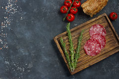 Συστατικά για το σάντουιτς, το ψωμί, τις ντομάτες, το λουκάνικο και το εκλεκτής ποιότητας μαχαίρι σε έναν ξύλινο πίνακα και ένα σ Στοκ Εικόνες