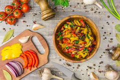 Συστατικά για το σκόρδο πιπεριών κρεμμυδιών τροφίμων και εργαλεία σε έναν ξύλινο πίνακα τοπ άποψη των πρασίνων λαχανικών πιάτων,  Στοκ Εικόνες