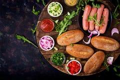 Συστατικά για το χοτ-ντογκ με το αγγούρι, την ντομάτα και το κόκκινο κρεμμύδι στο ξύλινο υπόβαθρο Στοκ φωτογραφία με δικαίωμα ελεύθερης χρήσης
