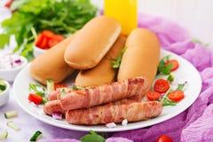 Συστατικά για το χοτ-ντογκ με το λουκάνικο μπέϊκον, αγγούρι, ντομάτα και κόκκινο κρεμμύδι Στοκ Φωτογραφίες