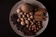 συστατικά για το ψήσιμο, ραβδιά κανέλας, γλυκάνισο αστεριών, γαρίφαλα, καρύδια, καρύδα, φασόλια καφέ σε ένα ξύλινο υπόβαθρο στοκ εικόνα