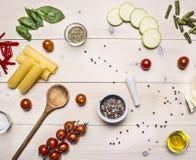 Συστατικά για το cannelloni ζυμαρικών μαγειρέματος, τις ντομάτες κερασιών, τα κολοκύθια και την unground ξύλινη αγροτική τοπ άποψ στοκ φωτογραφία