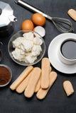 Συστατικά για το tiramisu μαγειρέματος - μπισκότα, mascarpone, κρέμα, ζάχαρη, κακάο, καφές και αυγό μπισκότων Savoiardi στοκ εικόνα