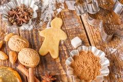 Συστατικά και φόρμες για την κατασκευή των κλασικών μπισκότων πιπεροριζών σε έναν ξύλινο πίνακα στοκ εικόνα