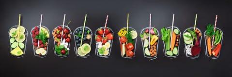 Συστατικά τροφίμων για το συνδυασμό του καταφερτζή ή του χυμού στο χρωματισμένο γυαλί πέρα από το μαύρο πίνακα κιμωλίας Τοπ άποψη στοκ εικόνα