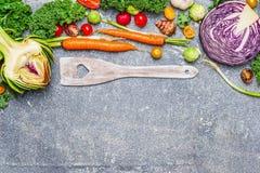 Συστατικά φρέσκων λαχανικών και ξύλινο μαγειρεύοντας κουτάλι με την καρδιά στο γκρίζο αγροτικό υπόβαθρο, τοπ άποψη Στοκ Εικόνες