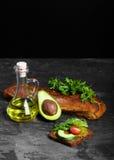 Συστατικά φρυγανιάς αβοκάντο σε ένα μαύρο επιτραπέζιο υπόβαθρο Χορτοφάγος έννοια προετοιμασιών μαγειρέματος προγευμάτων διάστημα  Στοκ εικόνα με δικαίωμα ελεύθερης χρήσης