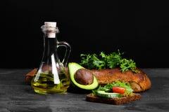Συστατικά φρυγανιάς αβοκάντο σε ένα μαύρο επιτραπέζιο υπόβαθρο Χορτοφάγος έννοια προετοιμασιών μαγειρέματος προγευμάτων διάστημα  Στοκ φωτογραφίες με δικαίωμα ελεύθερης χρήσης