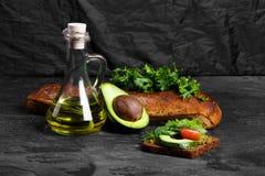 Συστατικά φρυγανιάς αβοκάντο σε ένα μαύρο επιτραπέζιο υπόβαθρο Χορτοφάγος έννοια προετοιμασιών μαγειρέματος προγευμάτων διάστημα  Στοκ φωτογραφία με δικαίωμα ελεύθερης χρήσης